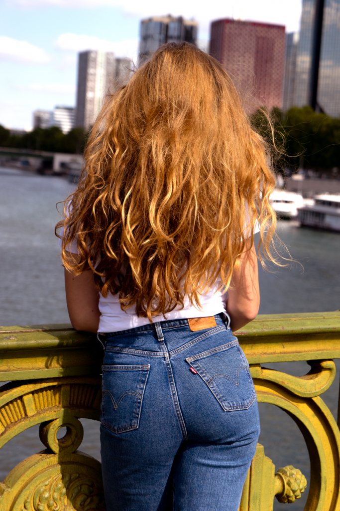 Agathe Sorlet avec le t-shirt en collaboration avec The Simones, de dos sur un pont