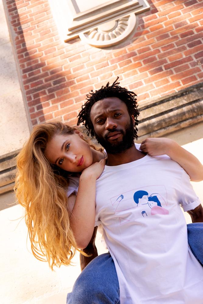 Agathe Sorlet sur le dos d'un modèle homme avec les t-shirts d'Agathe Sorlet face à un mur en brique